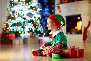 Kids at Christmas tree. Children open presents