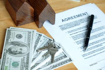 Dollar, model house, house keys and pen on agreement document.