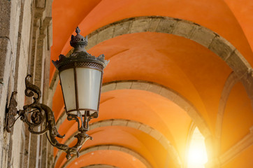 Antique wall lamp on arch background at Royal Palace in Naples, Italy. Copy space
