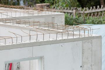 Baustellendetails mit frisch gegossenen Betonwänden und Armierungseisen