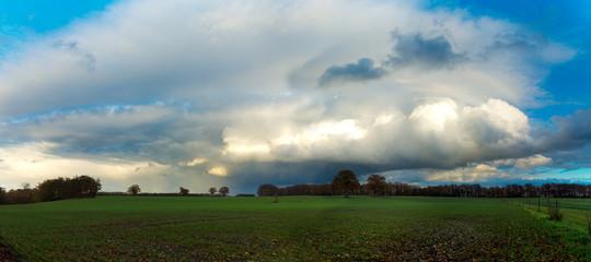Landschaft  mit Gewitterwolken nach Unwetter über einem Feld