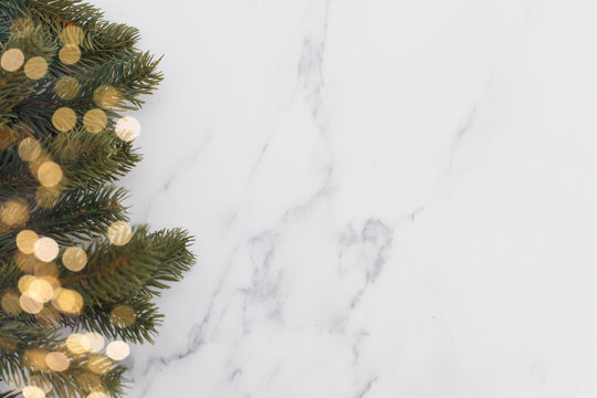 Christmas fir tree branches and bokeh blurred fairy lights on a marble background