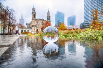 WARSAW, POLAND - NOVEMBER 3, 2018: Grzybowski Square is a triangular square in the downtown district of Warsaw, Poland. View through a glass, crystal ball (lensball) for refraction photography.