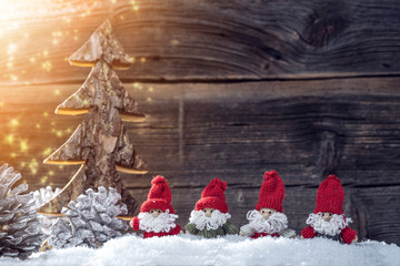 4 Santa Clause in the snow with light sparkles in the background