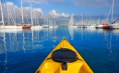 Kayak sailing in a marina port with boats