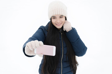 girl with a smartphone calls a friend in the park on a winter day