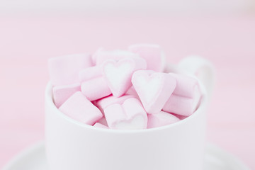 Cup of pink marshmallow hearts on a pink background. Valentines day love concept. Copy space