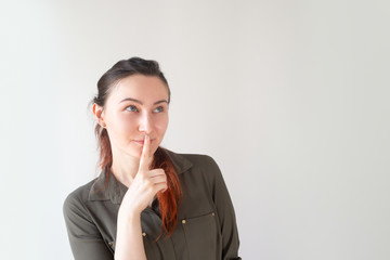 Portrait of happy Caucasian woman holding finger near mouth and smiling. Young female client looking up at copyspace. Wellness and beauty secret concept