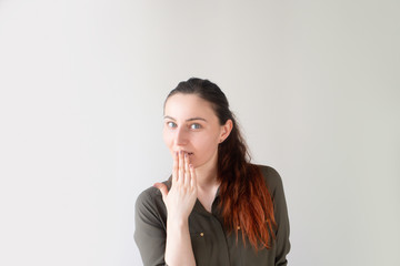 Portrait of shocked pretty Caucasian girl covering open mouth. Young female manager reacting to change of plans. Unexpected announcement concept