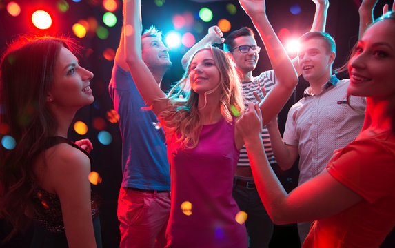 Group of young people having fun dancing at party.