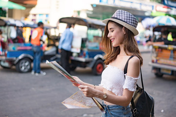 travel guide, tourism in Thailand , woman tourist with map on the street.