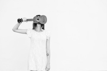 Black and white shot of Happy young woman closing face with ukulele at the background of a white wall. Musical concept.