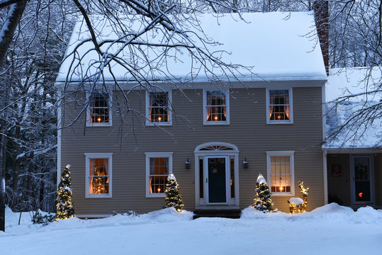 House in the forest with glowing windows and candles and a Christmas tree. The atmosphere of the holiday of Christmas and the new year.