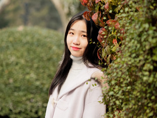 Portrait of beautiful young brunette woman in white winter fluffy coat. Outdoor fashion glamour Chinese teenage stylish lady. Emotions, people, beauty and lifestyle concept.