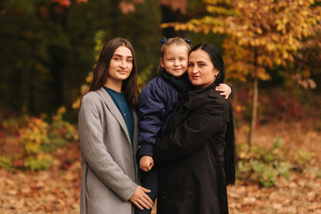 Portrait of happy family in autumn park. Mothe with two daughter. Two sister with mom
