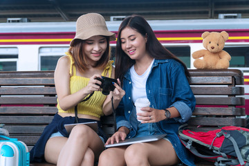 Travel and lifestyle concept. Two young woman friends watching photos on digital camera in the station. Traveller cheerful girl watching shocked photos on camera laughing at the railway station.