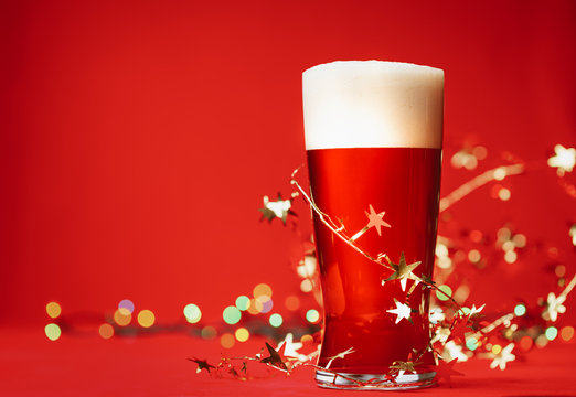 Pale ale or beer in pint glass with christmas lights and tinsel on red background