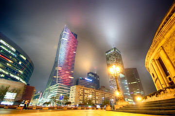 WARSAW, POLAND - NOVEMBER 3, 2018: Modern skyscrapers in the downtown district of Warsaw, Poland. A view from street level during the foggy night.