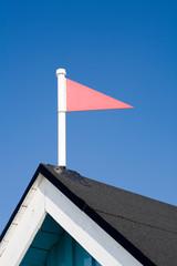 red triangular wind vane against blue sky