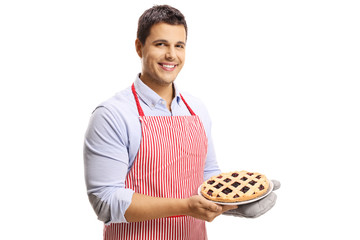 Handsome man with apron holding a cherry pie