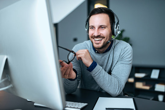 Happy business man with headset at workplace in front of the computer.