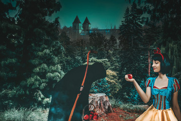 Snow White girl with old evil witch gives her an apple in the mysterious forest closeup. Artistic processing Fotomurales