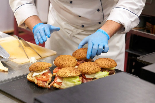 The chef prepares many hamburgers on the table in the restaurant.