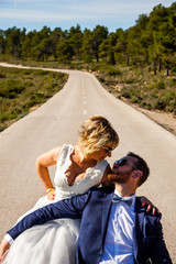 Couple of newlyweds pose in romantic attitude in the middle of a lonely road