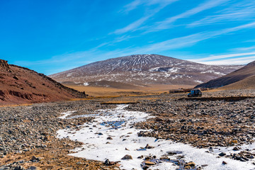 View of a village in the valley of beautiful mountain in Mongolia with the animal grazing and the frozen stream