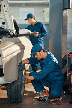 Service worker fixing a wheel of a car with his partner working in the background