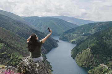 Woman taking selfie with the river in the background. Wall mural