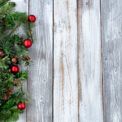 Christmas background with evergreen branches and red ornaments on aged white wood