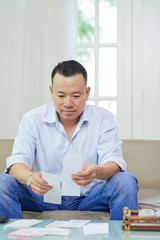 Concentrated man sitting before receipts on the table and analyzing his income and expenses at his home