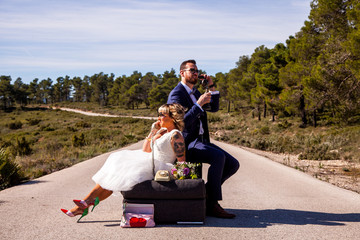 Newlywed couple pose on their sofa in the middle of a lonely road with vintage phones