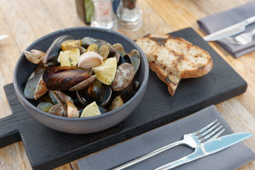 Boiled shellfish in deep clay plate