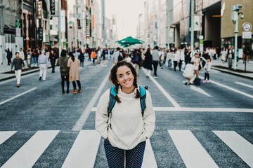 .Caucasian middle-aged woman traveling through Japan. Touring the city of Tokyo in one of the neighborhoods with more shops. Lifestyle.