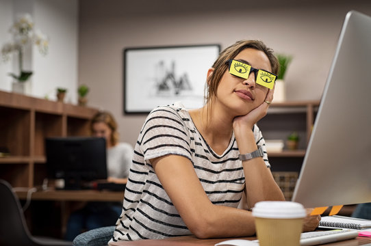 Tired woman covering eyes with post it