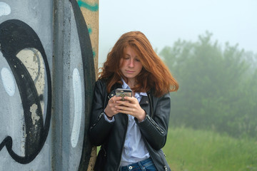 Italy, Finale Ligure, portrait of red headed teenage girl leaning against mural looking at cell phone