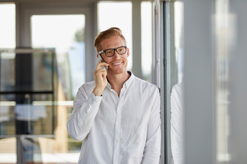 Smiling businessman on the phone at the window in office