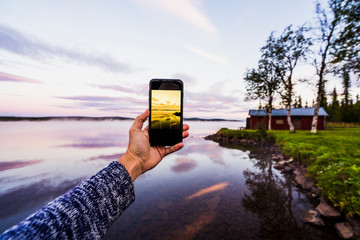 Sweden, Lapland,  Person taking a smartphone picture of the sunset