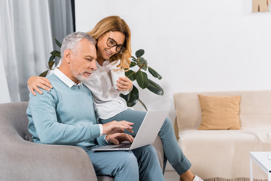 side view of middle aged man using laptop while his smiling wife sitting near with coffee at home