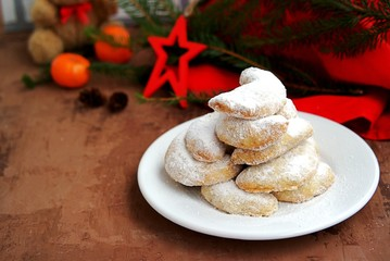 Shortbread with walnuts, covered with powdered sugar, on a white plate in the New Year and Christmas style. Merry christmas and happy new year concept.
