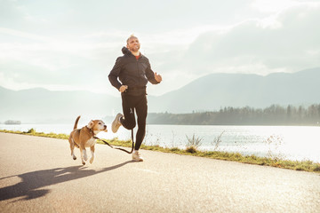 Morning jogging with pet: man runs together with his beagle dog Wall mural