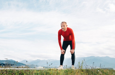 The wide angle shoot of a Man dressed in red long sleeve shirt very tired after the jog  by the road with mountain background and resting to lean forward.