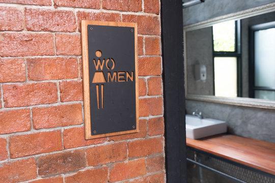 Women signs on public restroom on brick wall