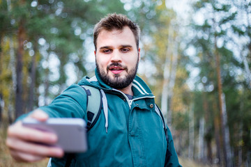 handsome male hiker taking a selfie in a forest