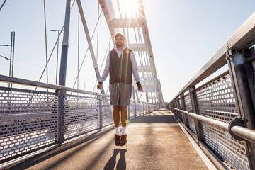 Sports man jumping with skipping rope at bridge