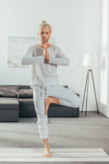 adult man standing in tree pose with namaste gesture on yoga mat at home