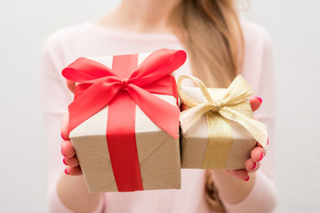 Woman holding a box with a gifts, gift with red ribbon, gift with gold ribbon, on camera, front view, close up