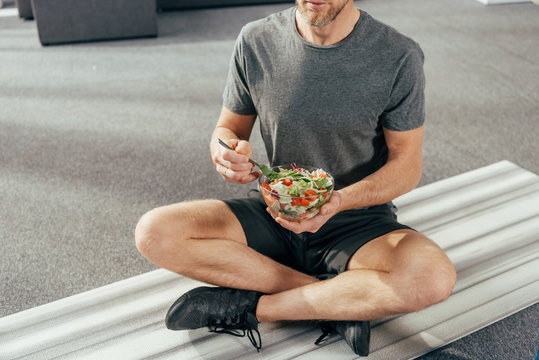 cropped shot of athletic man in sportswear sitting on yoga mat and holding bowl with vegetable salad at home